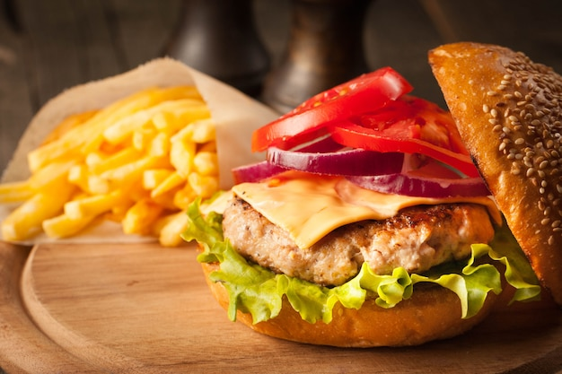 Hamburger fait maison avec boeuf, oignon, tomate, laitue et fromage. burger frais bouchent sur table rustique en bois avec frites de pommes de terre, bière et frites. cheeseburger.