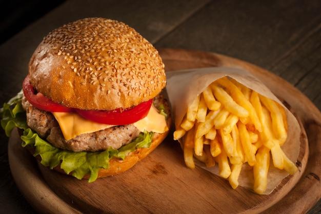 Hamburger fait maison avec du bœuf, de l'oignon, des tomates, de la laitue et du fromage.