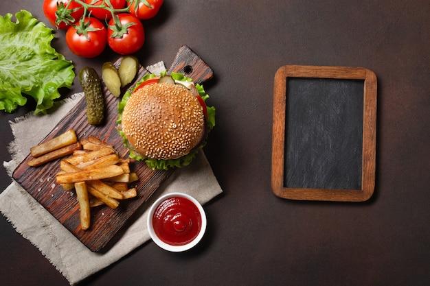 Hamburger fait maison avec du bœuf, des tomates, de la laitue, du fromage, des oignons, des concombres et des frites