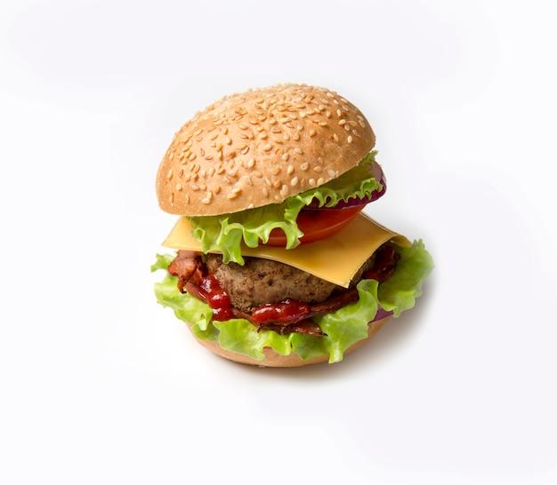 Hamburger fait maison sur fond blanc. hamburger aux graines de sésame et bacon, légumes verts et fromage.