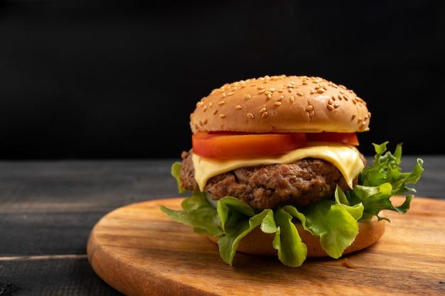 Hamburger fait maison savoureux frais avec des légumes frais sur une planche à découper.