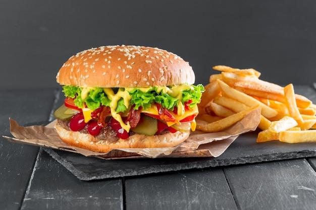Hamburger avec des frites sur une assiette en ardoise