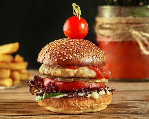 Hamburger avec galette de poulet sauce tomate concombres marinés tomates