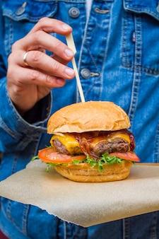 Hamburger en gros plan des mains mâles.