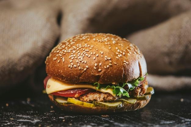 Hamburger gros plan sur la table noire sur le fond de la toile de jute délicieux juteux et chaud