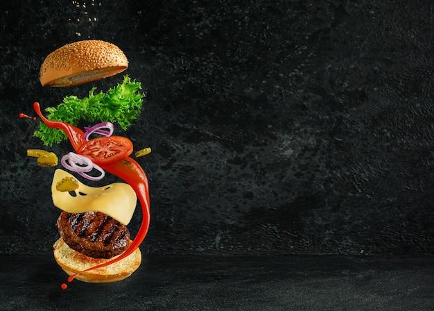 Hamburger avec des ingrédients flottants sur l'obscurité. concept de nature morte créative et publicité