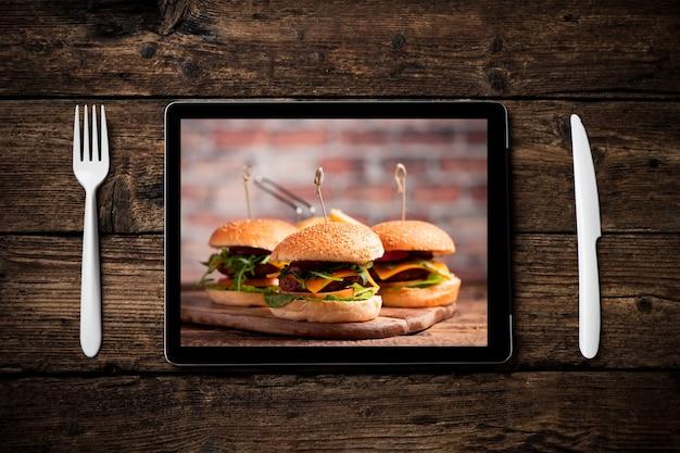 Un hamburger avec laitue, fromage cheddar, oignons, tomate sur planche de bois affiché sur un tablet pc. concept de livraison de nourriture en ligne