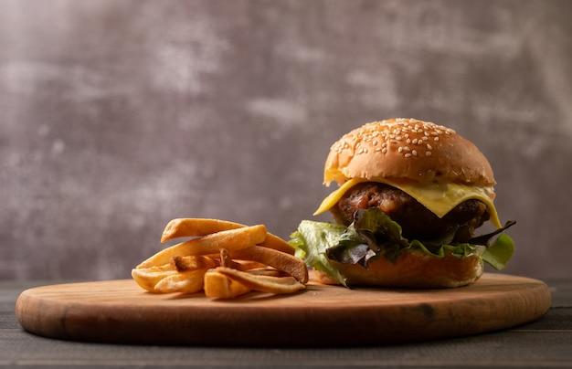 Hamburger maison savoureux frais avec des légumes frais et des frites.