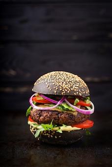 Hamburger noir avec hamburger de bœuf juteux, fromage, tomate et oignon rouge
