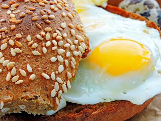 Hamburger avec des oeufs de caille. pain de seigle au sésame. fermer. pain chaud frais avec des oeufs de caille frits.