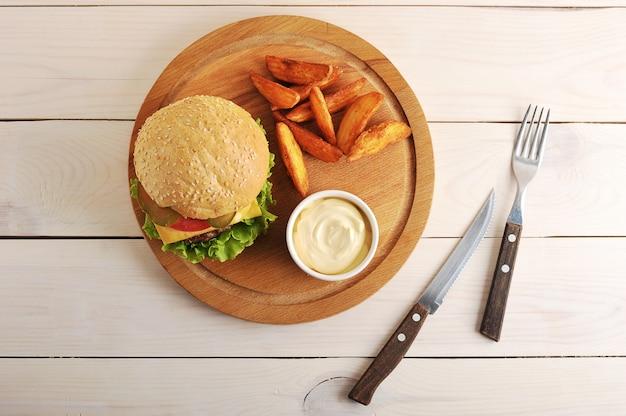 Hamburger avec pommes de terre idaho et sauce au fromage sur une planche de bois ronde
