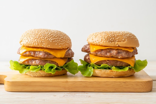 Hamburger de porc ou burger de porc avec du fromage sur planche de bois