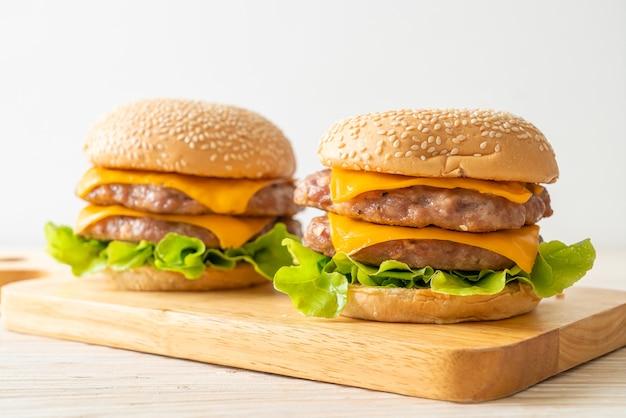 Hamburger de porc ou hamburger de porc au fromage sur planche de bois