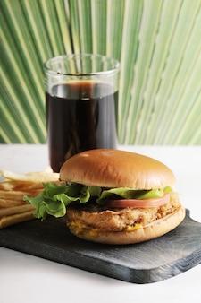 Hamburger rond avec côtelette de poulet et frites et un verre de coca