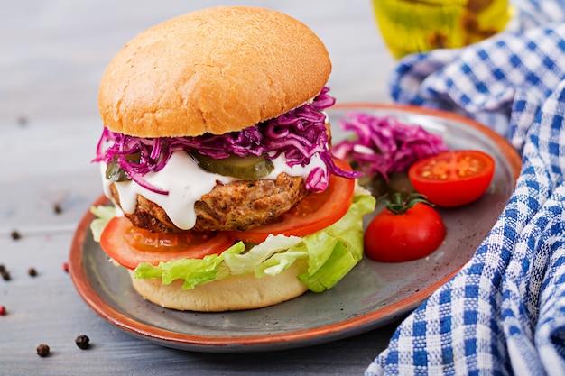 Hamburger sandwich avec hamburgers juteux, tomate et chou rouge