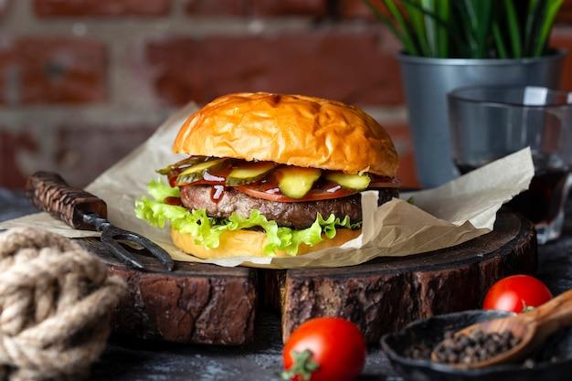 Hamburger savoureux fait maison avec des légumes frais sur une planche de bois
