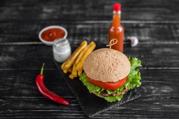 Hamburger savoureux avec de la viande et des légumes sur un fond sombre. fast food. il peut être utilisé comme arrière-plan