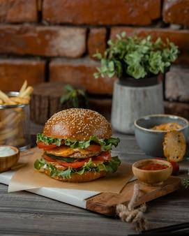 Un hamburger servi avec du cheddar fondu et du sumakh sur une table rustique