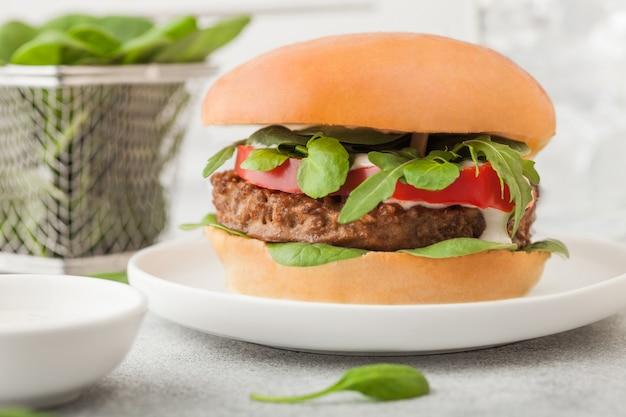 Hamburger végétarien sain sans viande sur une plaque en céramique ronde avec des légumes et des épinards sur une table lumineuse.