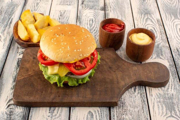 Un hamburger à la viande avec du fromage et des pommes de terre à salade verte et des trempettes