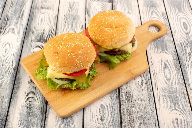 Un hamburger de viande vue de face avec fromage et salade verte sur la table en bois et table grise