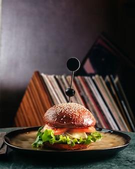 Un hamburger vue de face à l'intérieur d'une plaque ronde sur le sol sombre