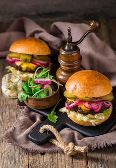 Hamburgers à angle élevé avec cornichons et oignon rouge sur une planche à découper