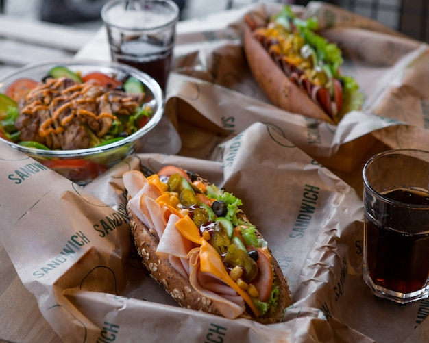 Hamburgers baguette avec boisson gazeuse sur un papier