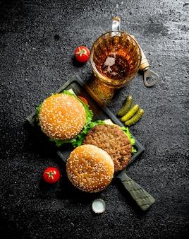 Des hamburgers et de la bière dans un verre. sur fond rustique noir