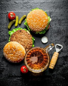 Des hamburgers et de la bière dans un verre sur une table rustique noire.