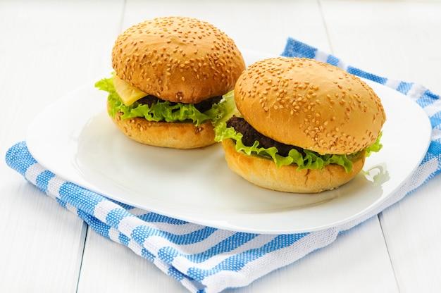 Hamburgers de bœuf faits maison sur assiette et serviette. fond en bois blanc