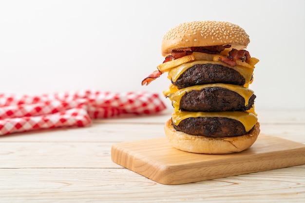 Hamburgers ou burgers de bœuf avec fromage, bacon et frites - style alimentaire malsain