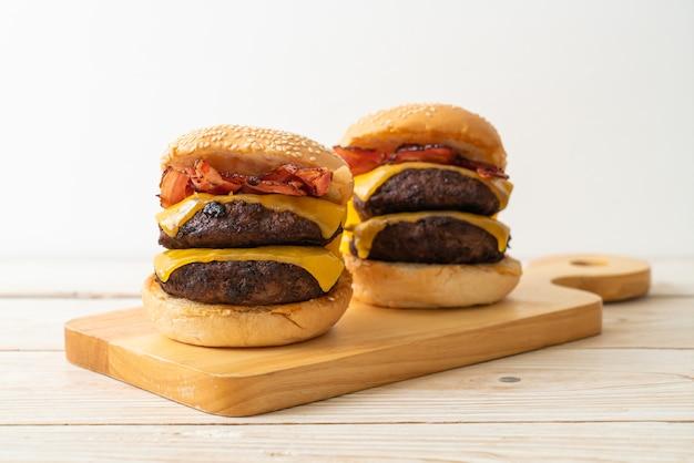 Hamburgers ou burgers de bœuf avec fromage et bacon - style alimentaire malsain