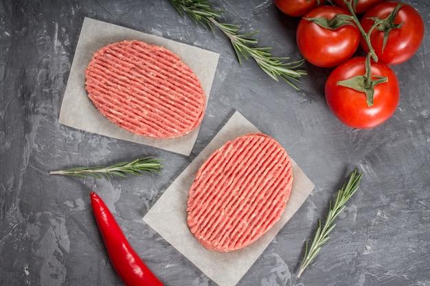 Hamburgers crus sur papier parchemin avec tomates, piments rouges et romarin.