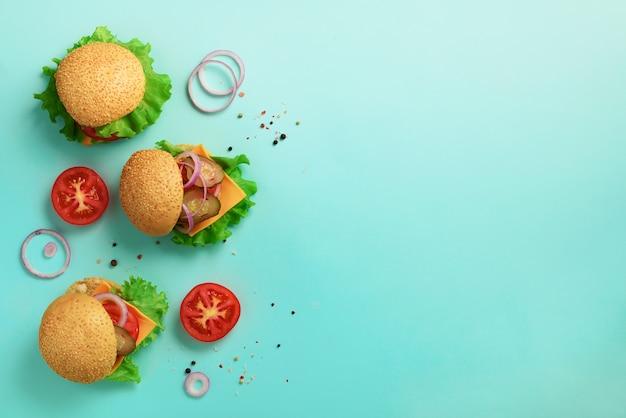 Hamburgers délicieux sur fond bleu. concept de régime malsain.