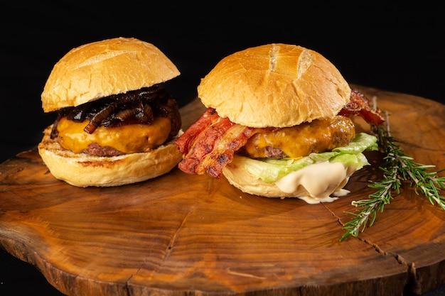 Hamburgers gastronomiques avec du fromage, de la laitue en sauce fondante. burgers bio sur une table en bois