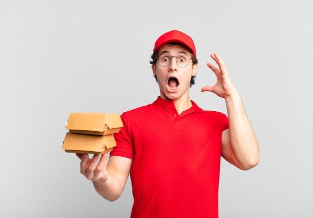 Des hamburgers livrent un garçon criant avec les mains en l'air, se sentant furieux, frustré, stressé et contrarié