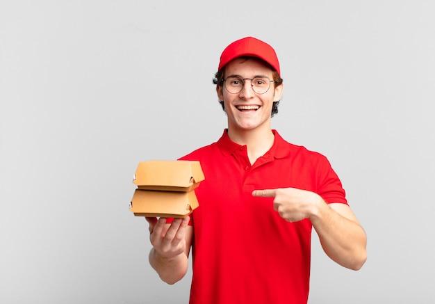 Les hamburgers livrent un garçon heureux, surpris et fier, se montrant lui-même avec un regard excité et étonné
