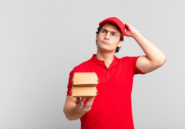 Les hamburgers livrent un garçon perplexe et confus, se grattant la tête et regardant sur le côté