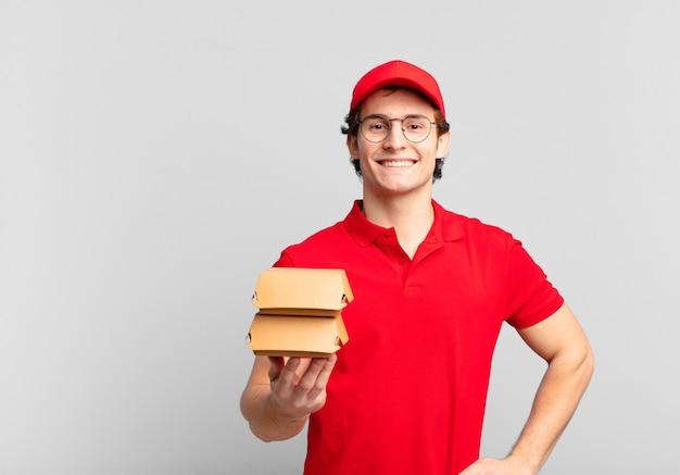 Les hamburgers livrent un garçon souriant joyeusement avec une main sur la hanche et une attitude confiante, positive, fière et amicale