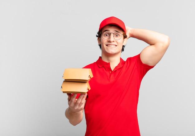 Les hamburgers livrent un garçon stressé, inquiet, anxieux ou effrayé, les mains sur la tête, paniqué par erreur