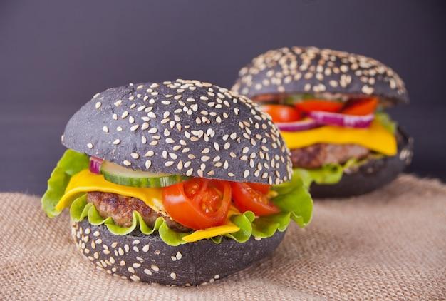 Hamburgers noirs faits maison avec une côtelette et des légumes sur la serviette