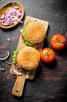 Des hamburgers sur la planche à découper et des tranches d'oignon dans le bol sur une table rustique.