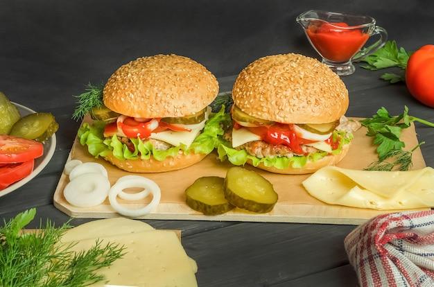 Hamburgers prêts à l'emploi avec des ingrédients sur une planche de bois sur un fond en bois noir.