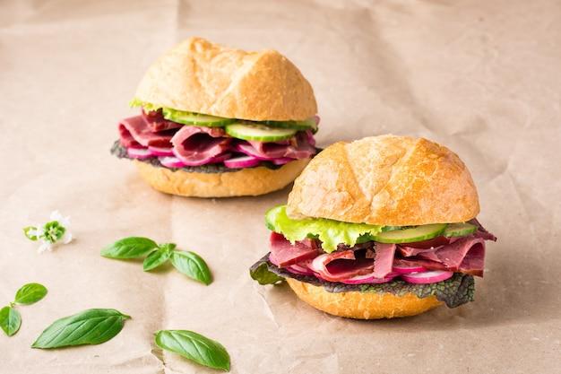 Hamburgers prêts à manger avec pastrami, concombre, radis et herbes sur papier kraft. restauration rapide américaine.