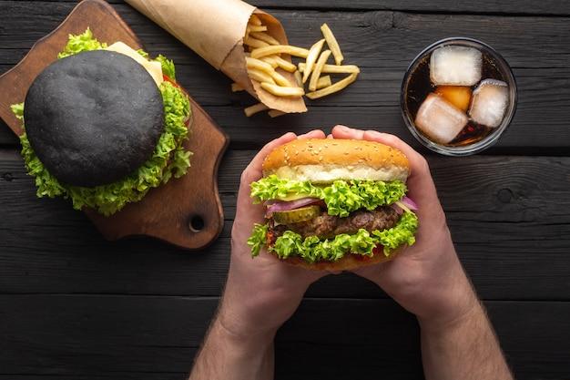 Des hamburgers savoureux frais avec des frites, boire sur la vue de dessus de table en bois.
