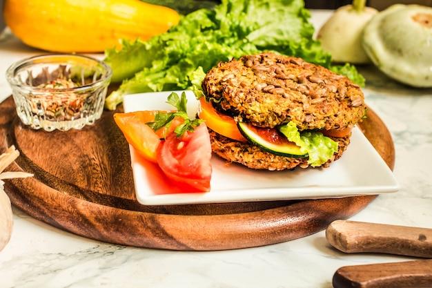 Des hamburgers végétaliens cuits au four avec des haricots et des graines, des légumes et des herbes.