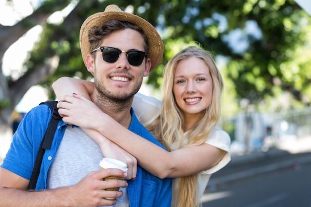 Hanche couple embrassant et souriant à la caméra à l'extérieur