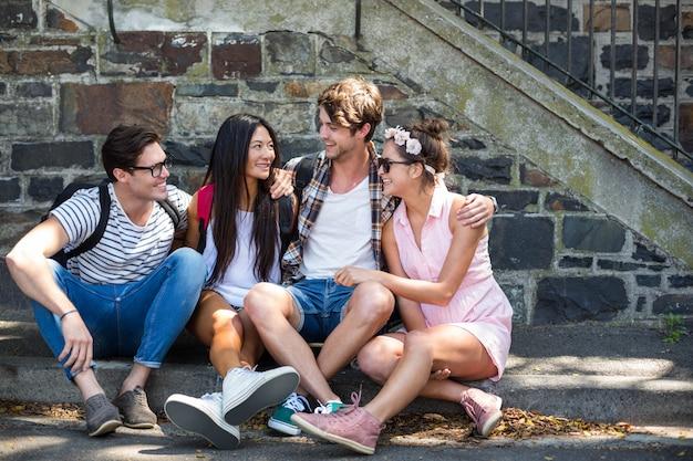 Hanches amis discutant et assis sur le trottoir en ville