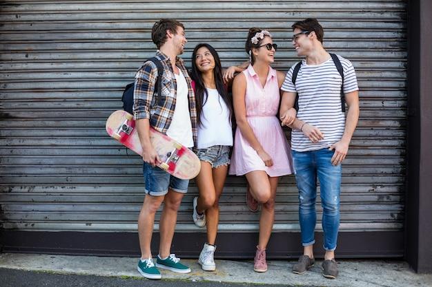 Hanches amis discutant et s'appuyant contre une porte roulante dans la rue